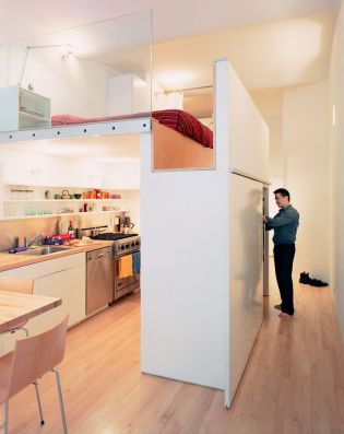 "Located in New York City's Union Square area, this 700-square-foot apartment features a bedroom lofted above a full kitchen. The volume that both incorporates the single closet (accessible from the hallway) and the refrigerator (which opens into the kitchen) and serves as the bedroom floor is, says resident Kyu Sung Woo, ""where everything comes together."" Photo by Adam Friedberg"